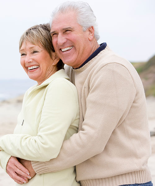 An elderly couple hugging on the beach