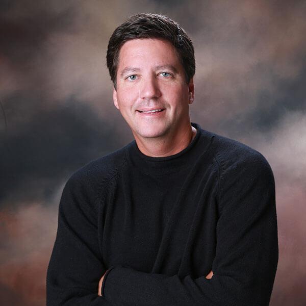 A portrait of Dr. Field in a black sweater