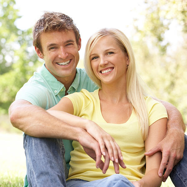 A young couple hugging and smiling in a park