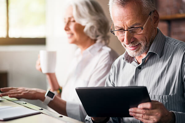 An older couple sitting at a desk while having coffee and using a tablet