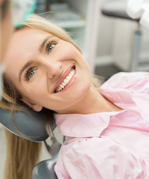 A woman looking up at her dentist from the dental chair