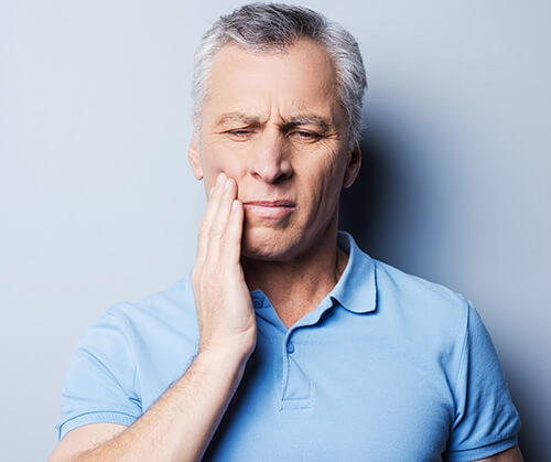 A man holding his jaw due to tooth pain